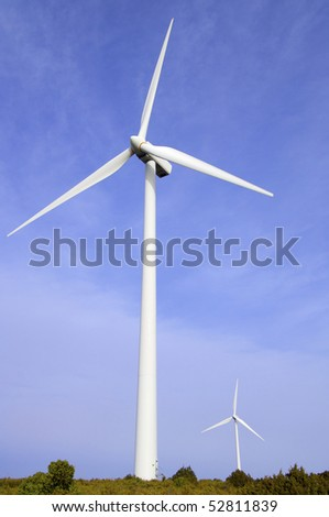 two windmills with blue and cloudy sky