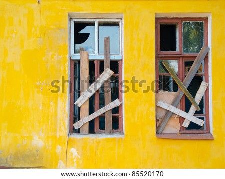 Two windows boarded up with boards in the yellow wall - stock photo