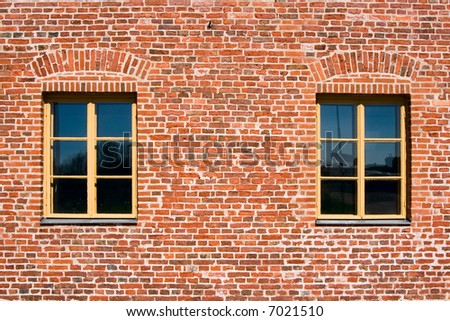 Two windows in a brick wall - stock photo