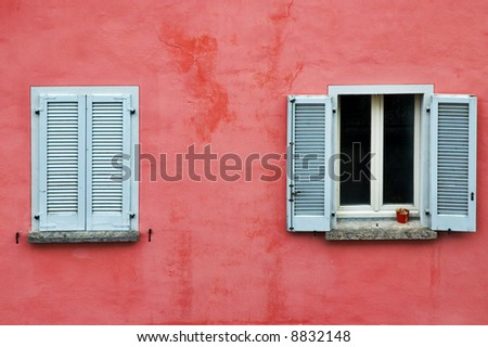 Two windows on a pink wall, one with white shutters closed