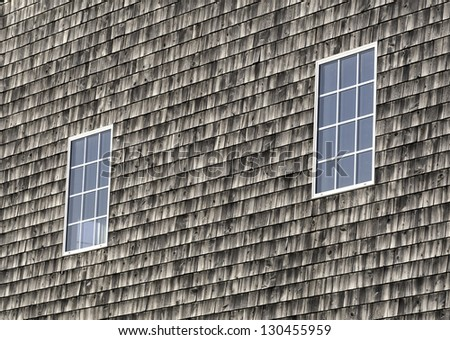 Two windows on an exterior wall with aged cedar shingle siding. - stock photo