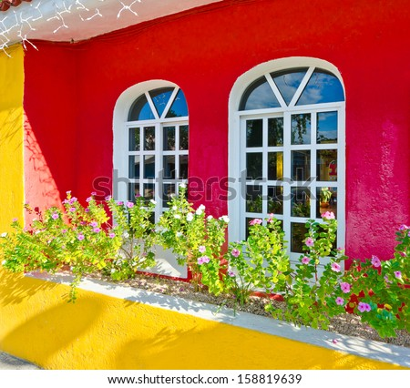 Two windows on the colorful red wall and some flowers. Mediterranean, Caribbean style. - stock photo