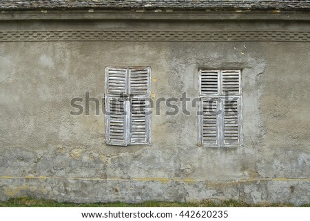Two windows on the wall of an old house in Seleus, Banat, Serbia - stock photo