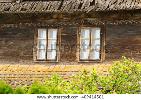 Two windows with curtains on old wooden house