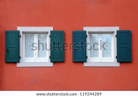 Two windows with shutters against ochre house wall background in Italy