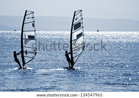 Two windsurfers In Red Sea, toned photo - stock photo