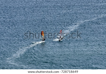Two windsurfers on the waves of the Mediterranean sea at Cape Prasonisi, Rhodes (Greece)