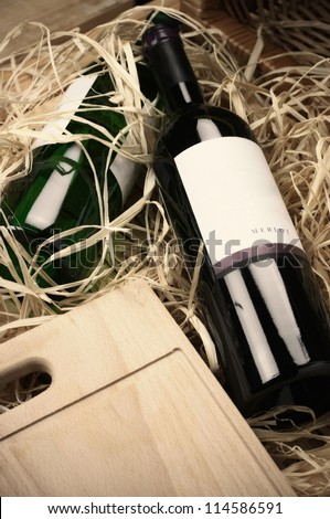 Two wine bottles lying in wooden box with straw. - stock photo