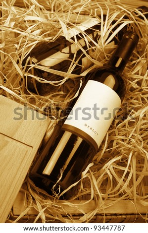 Two wine bottles lying in wooden box with straw. Monochrome toned image. - stock photo