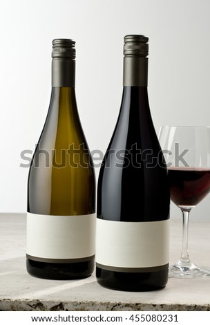 Two wine bottles on stone surface with glass, glass has red wine in it