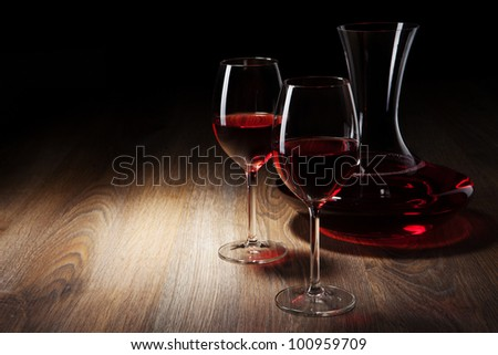 two Wine glass and decanter on a wooden table - stock photo