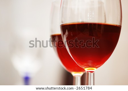 Two wine glasses against the red background - stock photo