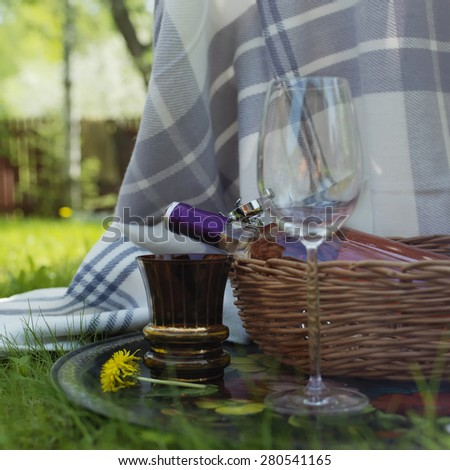 Two wine glasses and bottle of red wine in a basket, outdoor square shot - stock photo