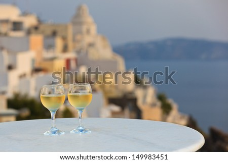 two wine glasses at sunset Santorini, Greece  - stock photo