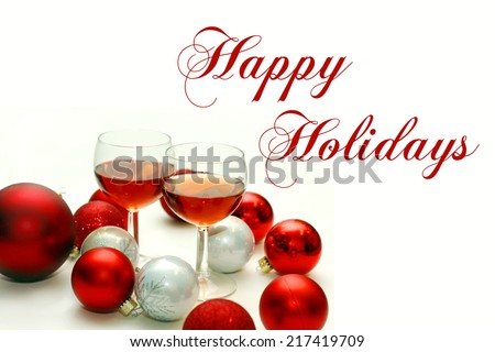 Two wine glasses filled with red wine sit isolated on a white background surrounded by red and white sparkly Christmas Bulbs, with the text Happy Holidays written in elegant cursive. - stock photo