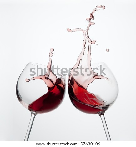 Two wine glasses in toasting gesture with big splashing. - stock photo