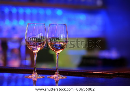 two wine glasses on a bar with beautiful ambient light