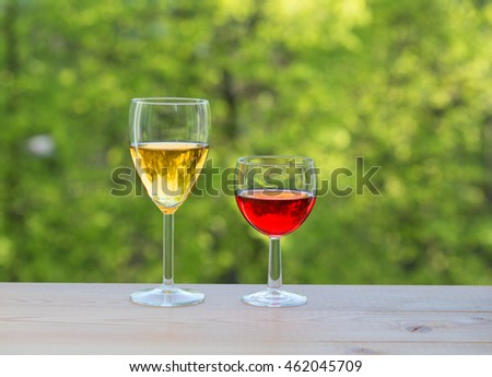 two wine glasses on table in the garden