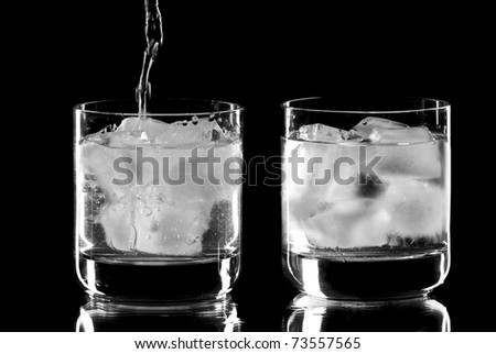 Two wine glasses with alcohol dropping into one of them. Black background. Studio shot. - stock photo