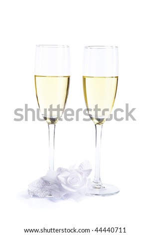 Two wine glasses with champagne and wedding flower on a white background