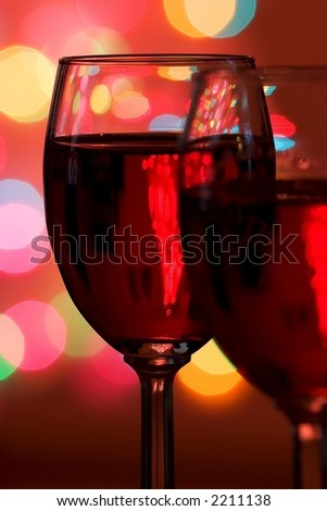 Two wine glasses with Christmas lights in the background - stock photo