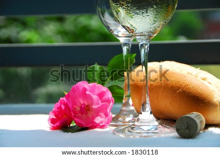 Two wine glasses with white wine, table setting outside - stock photo