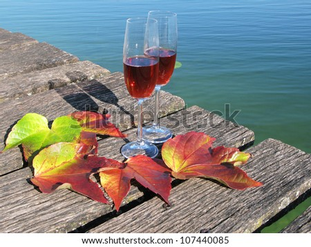 Two wineglasses and autumn leaves on a wooden jetty - stock photo