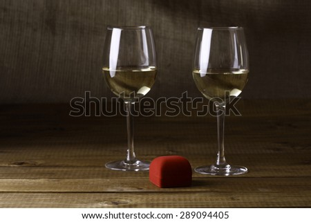 Two wineglasses of white wine with red velvet ring box on wooden table top on black background, horizontal picture - stock photo