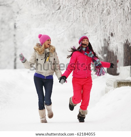 two winter women run by snow frosted alley - stock photo