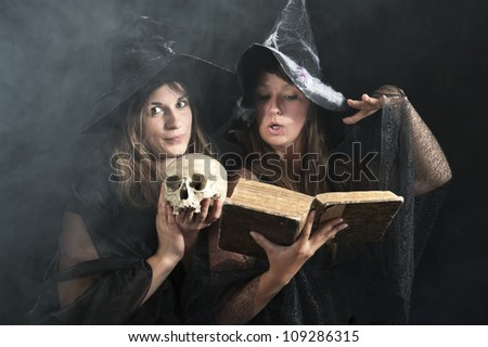 two witches with a book and skull - stock photo