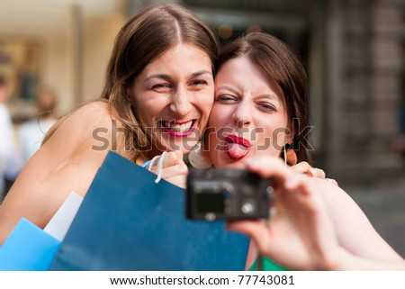Two woman being friends shopping downtown with colorful shopping bags and taking a picture from themselves ay - stock photo