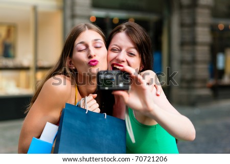 Two woman being friends shopping downtown with colourful shopping bags and taking a picture from themselves - stock photo
