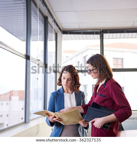 Two woman business colleagues standing in an office while looking seriously together and some paperwork in a folder in front of large windows - stock photo