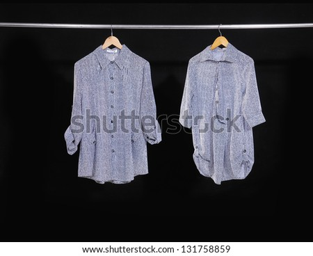 Two woman clothes on a hanger studio isolated on black - stock photo