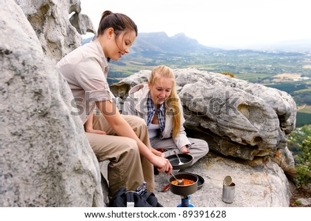 two woman cook some hiking food on a gas stove while sitting on top of a mountain - stock photo