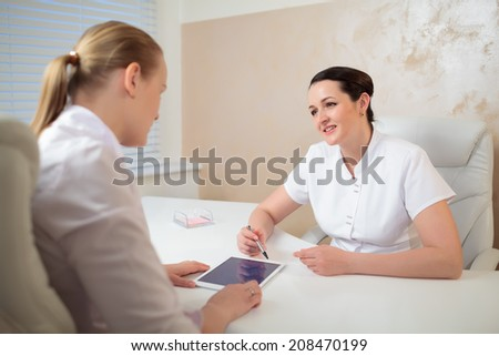 Two woman cosmeticians in the office room having a professional talk using pad
