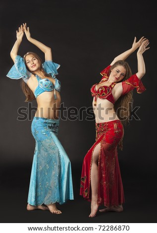 Two woman dance and smile in arabian costume