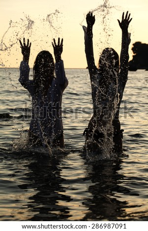 Two Woman dancing and spraying at the beach on beautiful summer sunset  - stock photo