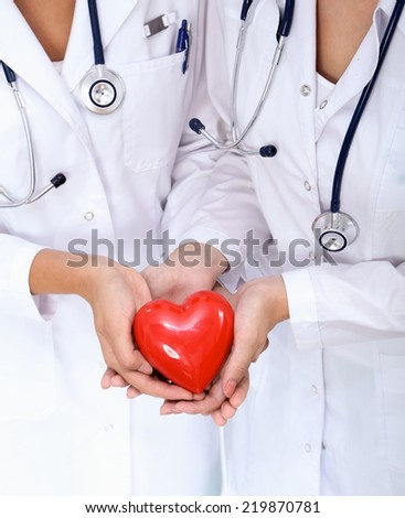 Two woman doctor holding a red heart, isolated on white background - stock photo