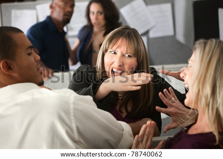 Two woman employees quarreling among other coworkers - stock photo