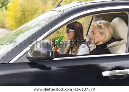 Two woman enjoying alcohol while driving in the countryside drinking directly from the bottles and posing a danger to others due to slowed reflexes - stock photo