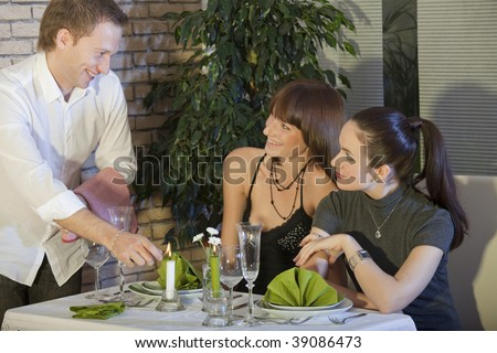 two woman flirting with waiter in a restaurant - stock photo