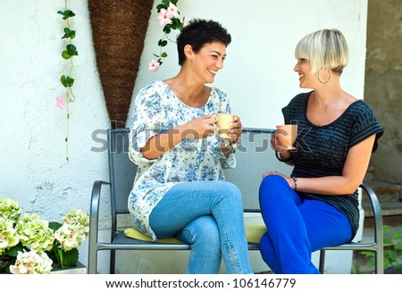 two woman friends chatting outdoors over coffee - stock photo