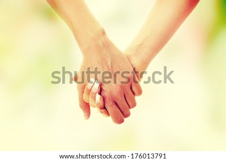 Two woman holding their hands