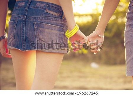 Two woman holding their hands - stock photo
