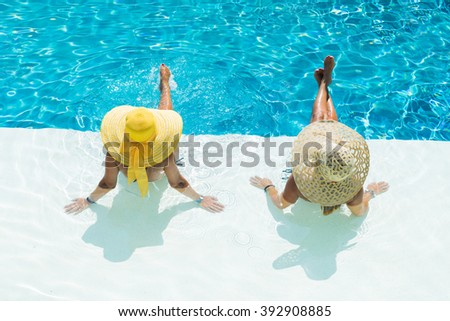 Two woman in a hat sitting on the edge of the swimming pool - stock photo