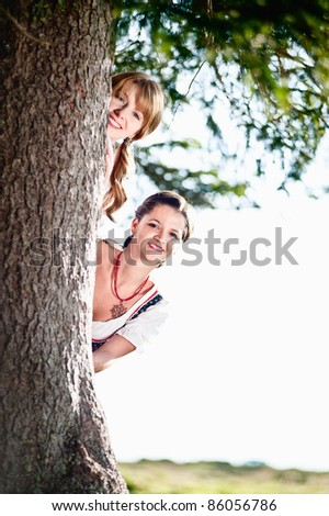 Two woman in dirndl hide behind a tree