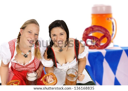 two woman in dirndl with beer mug and pretzel / Oktoberfest - stock photo