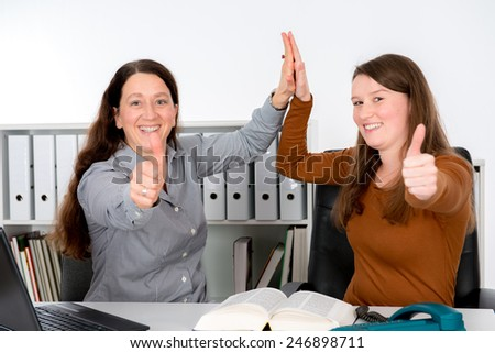 two woman in good teamwork in the office with thumb up - stock photo