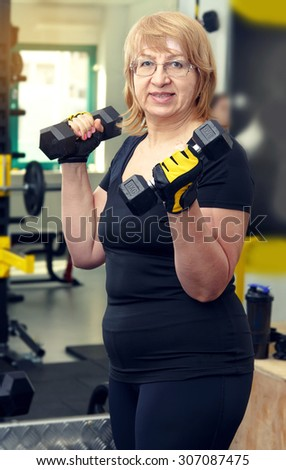 Two woman is engaged in a sports hall. Toned image. Women holding a dumbbell for fitness. Sporting women. Sports and fitness a lifestyle in all age. Pretty mature women, they client fitness club. - stock photo